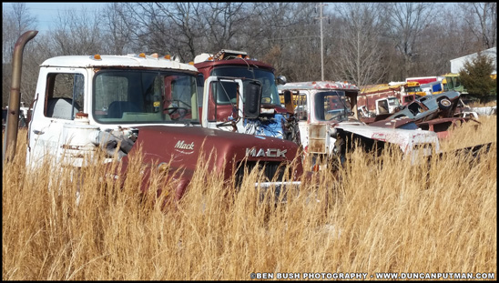 A couple of Mack R-Model trucks and other equipment sitting in a salvage yard in 2017 - Photo by Ben Bush