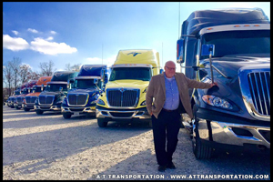 Mark Hagedorn stands with several of the A/T Transportation tractor-trailers